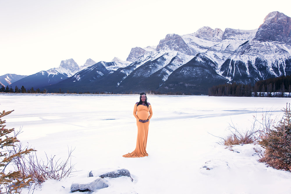 Gorgeous mommy-to-be wearing a mustard colour dress, standing on a snow and surrounded by Rocky Mountains in Canmore, Alberta, Canada. Calgary Maternity Photographer - Mountain Maternity Session in Alberta - Milashka Photography