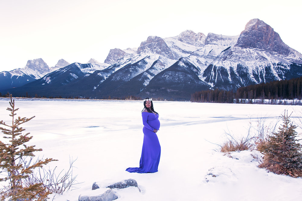 Calgary Maternity Photographer - Mountain Maternity Session in Alberta - Milashka Photography. Beautiful mother to be wearing a purple gown, standing on a snow, surrounded by Rocky Mountains in a beautiful Kananaskis Country, Canmore, Alberta, Canada.