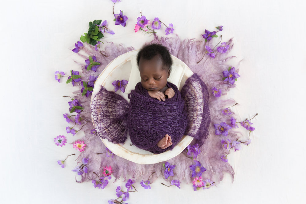 Newborn baby girl wrapped in a purple wrap, lying in the white wooden bowl, surrounded by purple flowers. Newborn Photoshoot ideas. Airdrie Newborn photographer. Milashka Photography