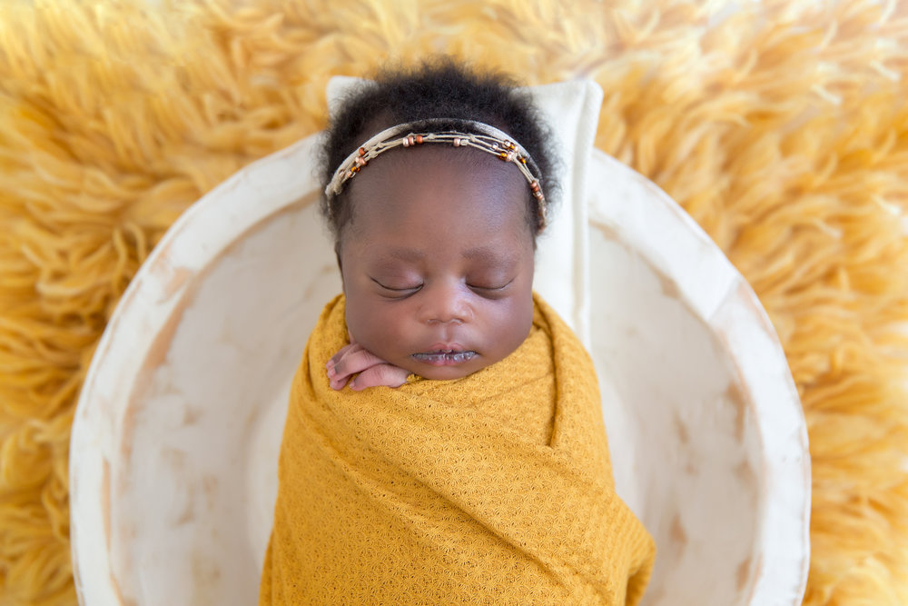 Newborn baby girl, wrapped in the mustard colour wrap, lying in the white wooden bowl. Newborn baby photoshoot ideas. Calgary and Airdrie newborn photographer