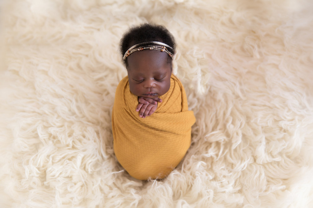 Potato sack pose - newborn baby girl wrapped in a mustard colour wrap on a bean bag and cream flokati rug. Newborn Photoshoot ideas. Calgary photographer specializing in Newborn and Maternity portraiture - Milashka Photography