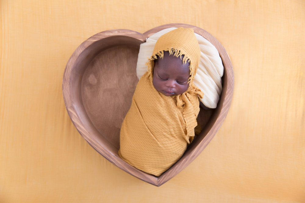 Newborn Baby girl, lying in a heart shaped bowl - newborn photography ideas. Calgary newborn photographer. Milashka Photography