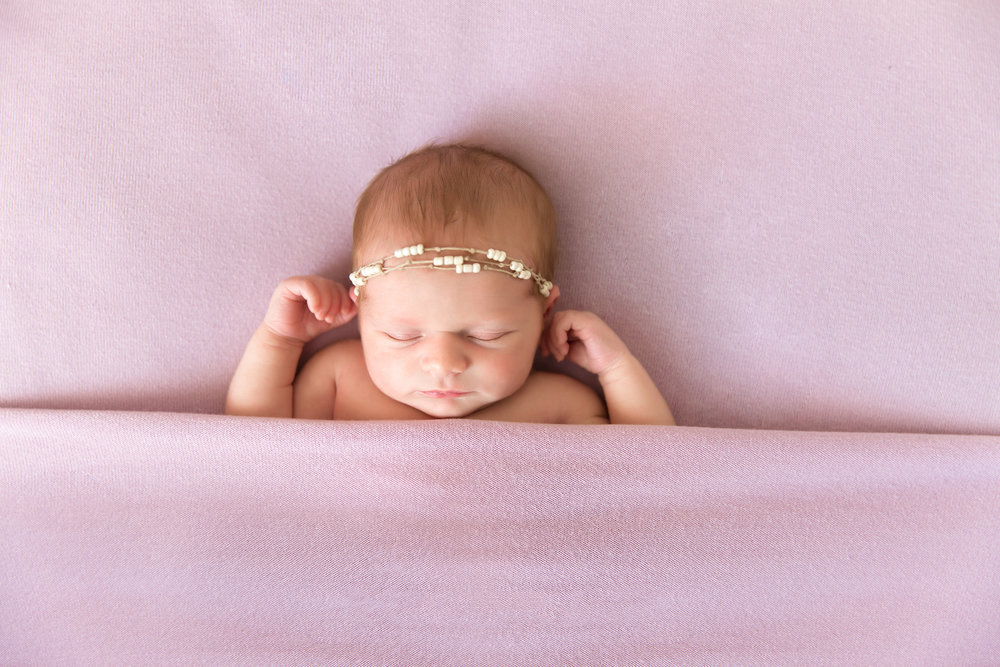 Tucked in pose on a beanbag. Newborn Photoshoot ideas. Newborn baby girl is photographed on a beanbag. Calgary Newborn Photographer. Milashka Photography