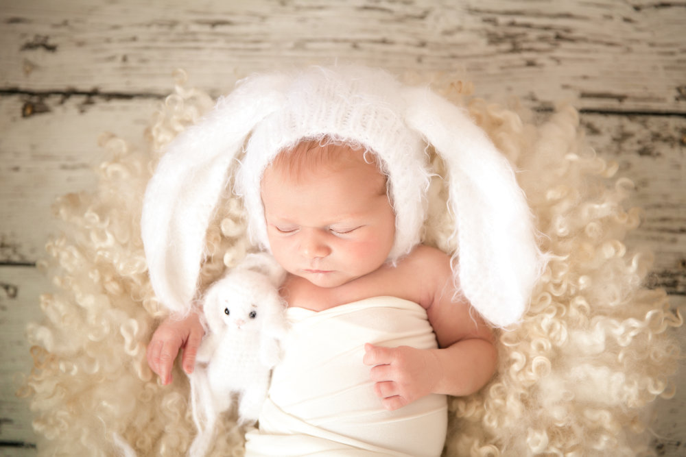 Newborn baby girl wearing a bunny hat and holding a bunny toy. Easter Newborn inspired photoshoot. Calgary Newborn Photographer. Milashka Photography