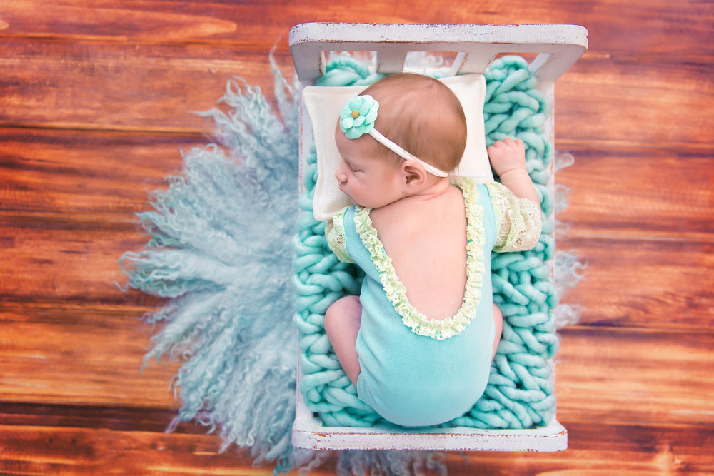 Newborn baby girl on a little bed in a cute mint outfit sleeping soundly. Newborn Photoshoot ideas. Calgary Newborn photographer - Milashka Photographer
