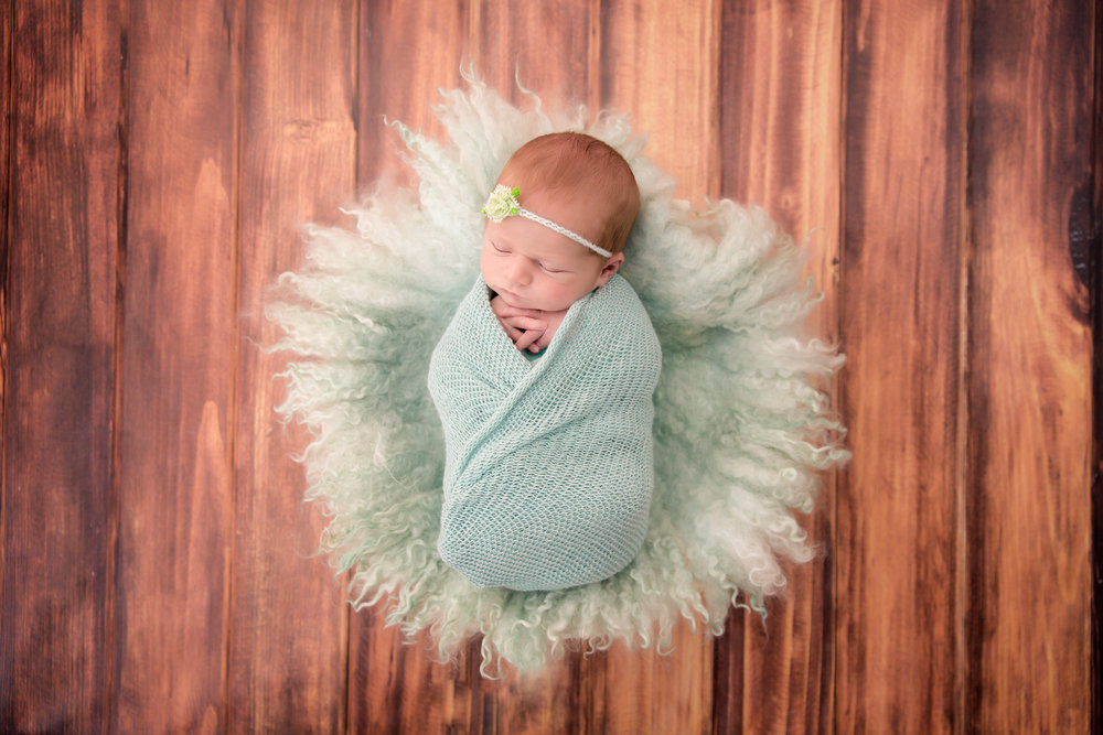Newborn baby girl is sleeping soundly in a mint nest, wrapped in a mint wrap. Newborn Photoshoot ideas. Calgary and Airdrie - Newborn Photographer - Milashka Photography
