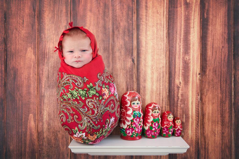 "Newborn baby girl wrapped as ""Matryoshka"" aka ""Russian doll"" with other Matryoshkas sitting on a shelf. Newborn Photoshoot ideas. Calgary Photographer - Newborn Photographer - Milashka Photography"
