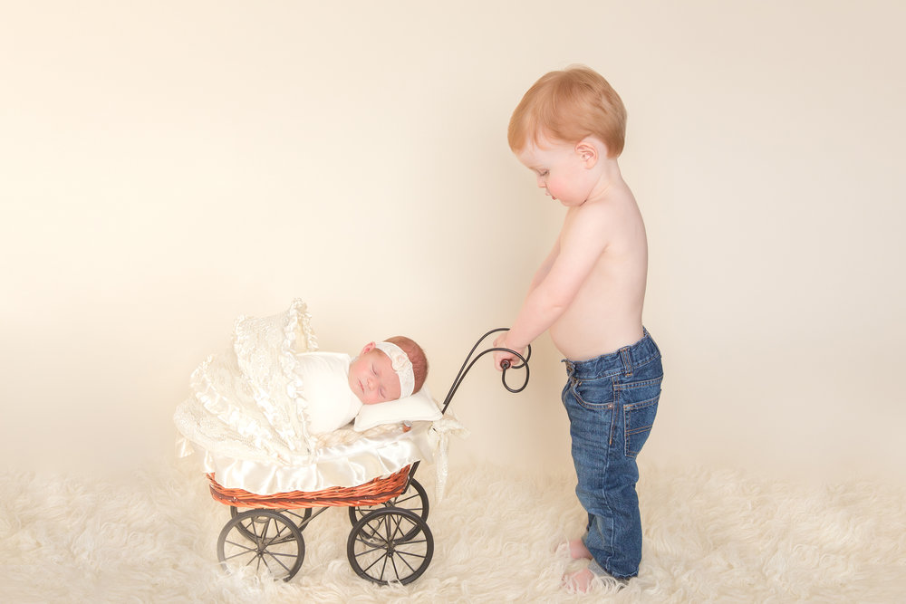 Big brother is looking at his newborn sister in a stroller. Siblings photoshoot. Newborn Photoshoot ideas with older siblings. Calgary Newborn photographer - Milashka Photography