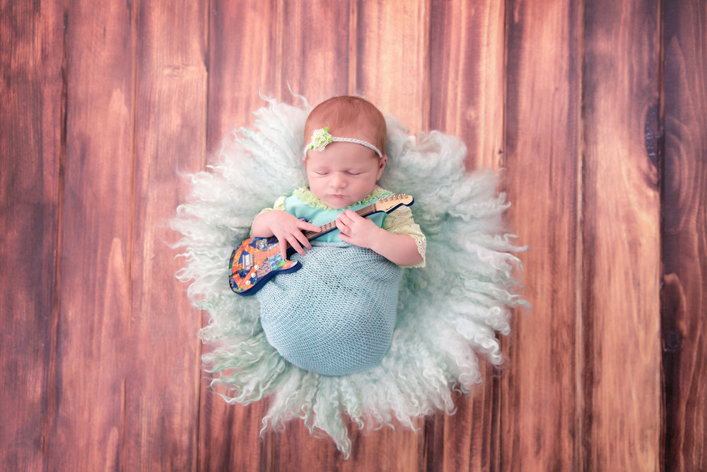 Newborn baby girl with a little guitar. Newborn Photoshoot ideas. Calgary based photographer - Milashka Photographer.