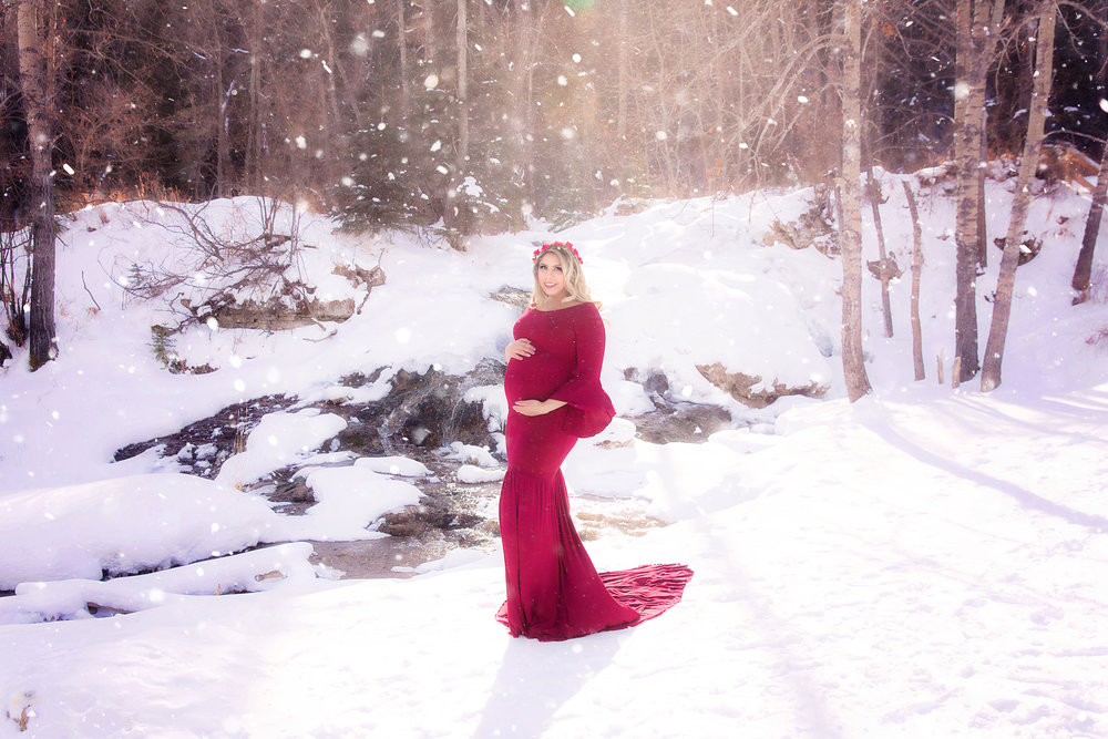 Stunning mom-to-be is standing on the snow wearing a red gown and a red flower crown, while it is snowing in the middle of February at the Big Hills Spring Provincial Park. Calgary Maternity Photographer - Milashka Photography