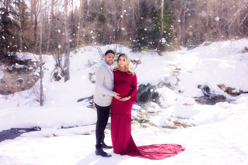 Radiant expecting parents are standing on the snow in the middle of a winter while it is snowing. Mom-to-be is wearing a gorgeous red gown. Winter Maternity Photoshoot ideas - Milashka Photography - Calgary Maternity Photographer