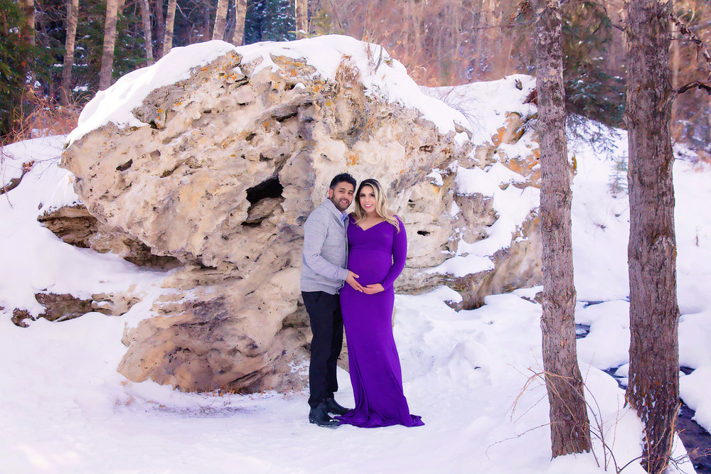 Expecting parents standing in front of a giant rock in the middle of a winter at the Big Hills Spring Provincial Park.