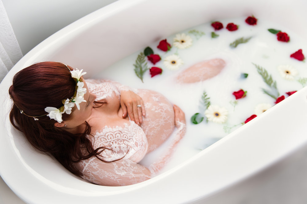 Mom-to-be sitting in a bathtub full of milk and flowers wearing a white lace dress. Milk bath maternity session ideas. Calgary milk bath maternity photographer - Milashka Photography