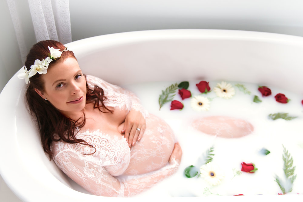 Milk bath maternity session. Beautiful mom-to-be sitting in a milk bathtub, surrounded by floating flowers and smiling. Milk bath ideas. Maternity milk bath photoshoot in Calgary and Airdrie, Alberta.