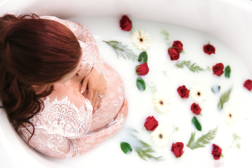 Milk bath photoshoot. Mom-to-be sitting in a bathtub full of milk and flowers. Calgary milk bath maternity photoshoot.