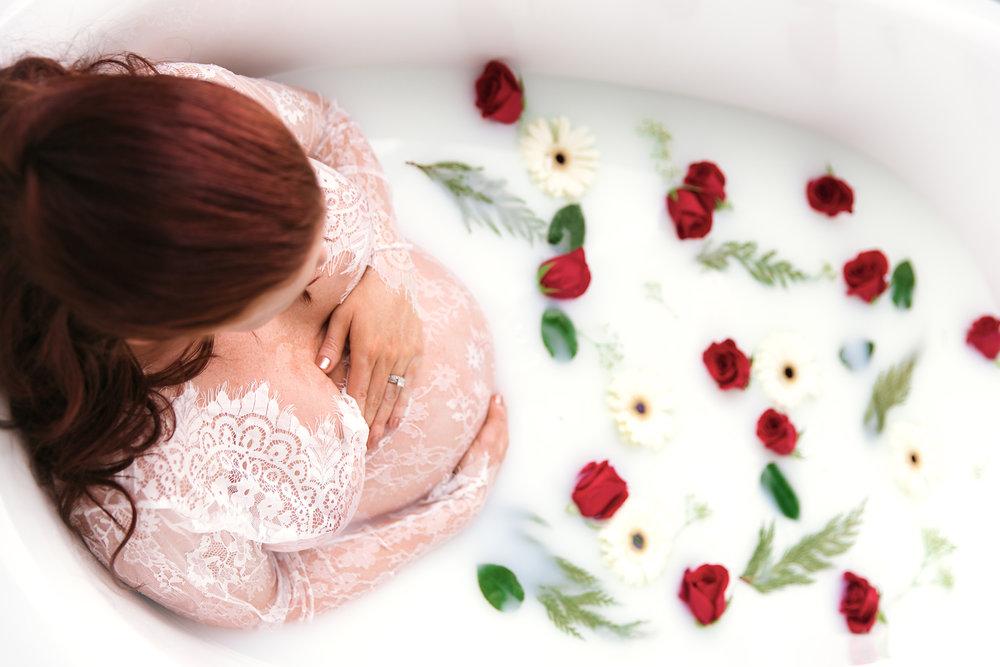 Milk bath photoshoot. Mom-to-be sitting in a bathtub full of milk and flowers. Calgary milk bath maternity photoshoot.