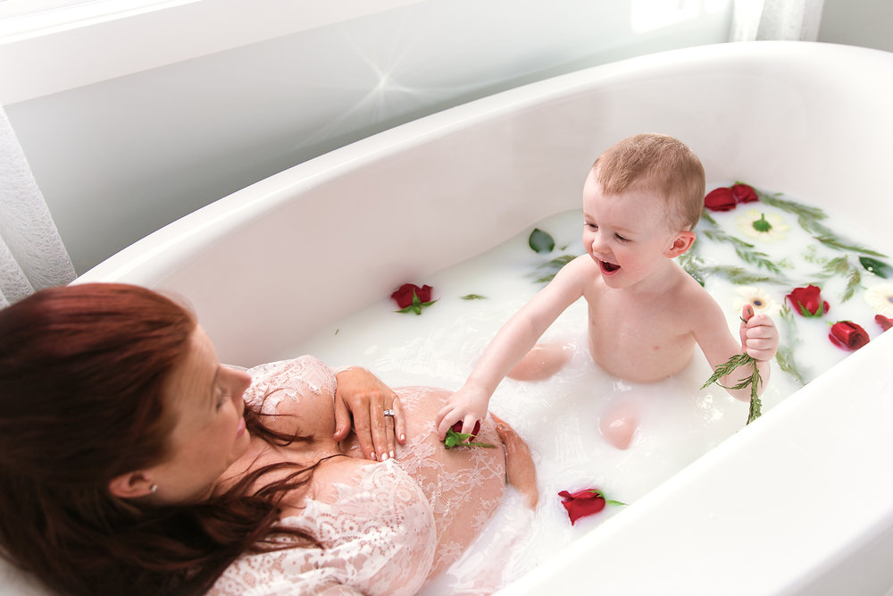 Mom-to-be and her toddler son are enjoying a milk bath during mom's milk bath maternity photoshoot. Calgary Maternity Photographer - Milashka Photography