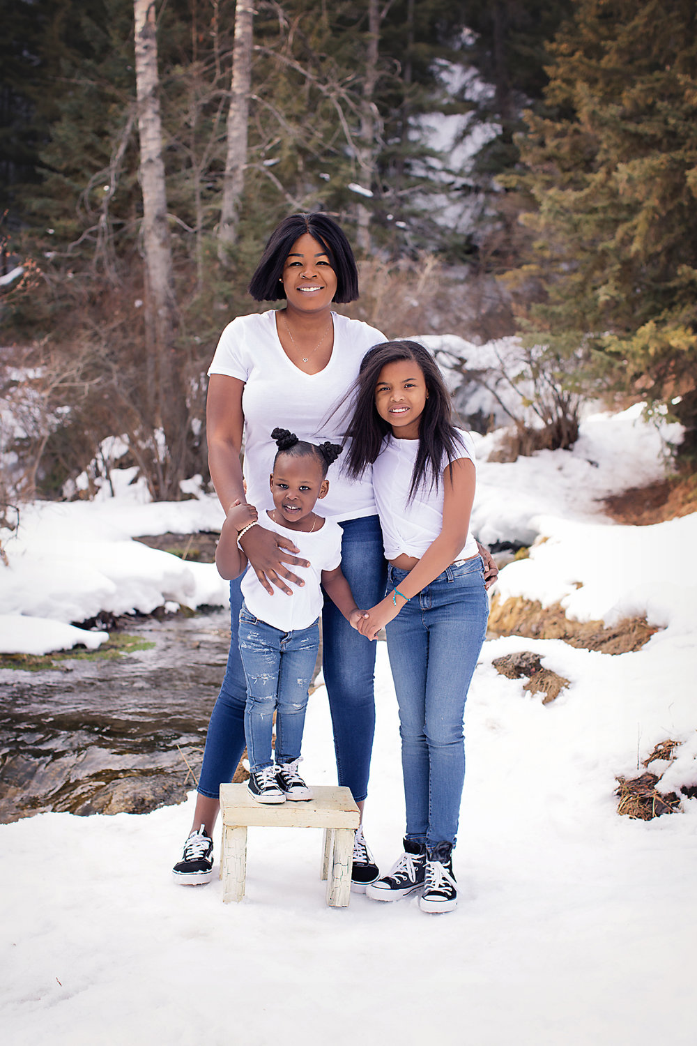 Mother and her daughters are standing in front of a beautiful waterfall in the winter at the Big Hill Springs Provincial Park. Calgary Family Photographer - Milashka Photography