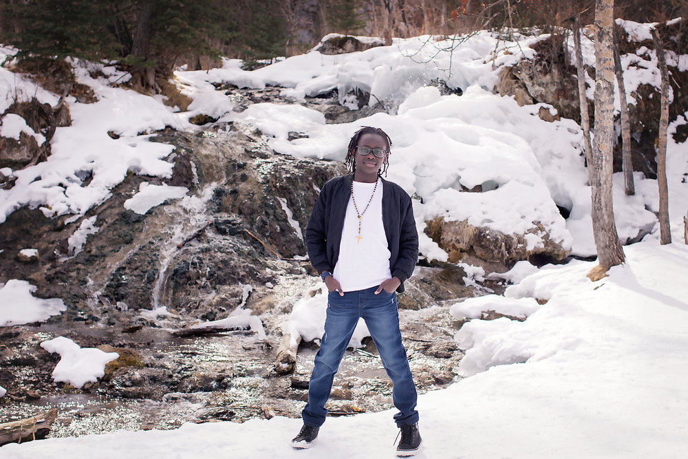 Portrait of a handsome young man standing in front of a waterfall in the snow at the Big Hill Springs Provincial Park. Calgary family photographer- Milashka Photography