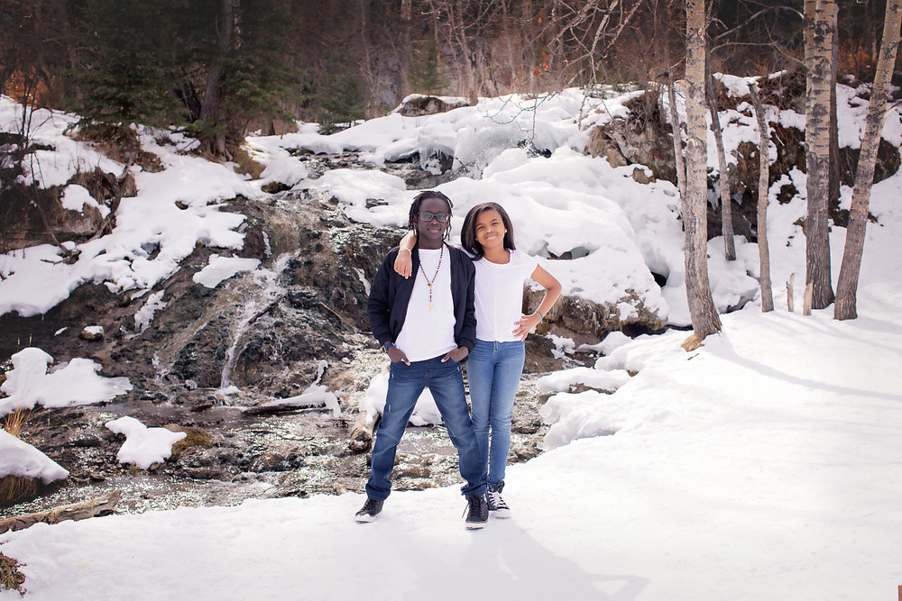 Cousins are standing in front of a waterfall at the Big Hill Springs provincial park. Calgary photographer - Milashka Photography