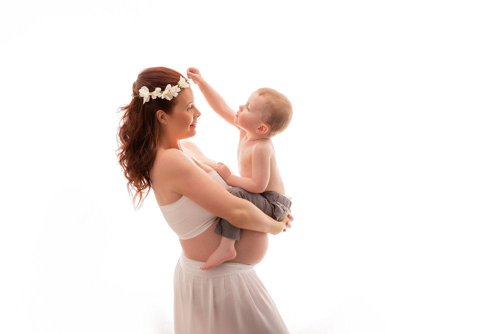 Mom to be and her toddler son in this backlit image. Calgary Maternity Photoshoot - Milashka Photography