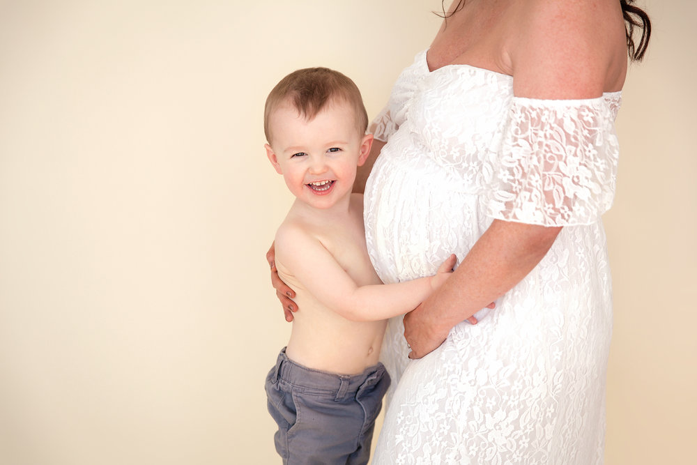 Big brother to be is hugging mommy's belly and smiling. Calgary photographer - Milashka Photography