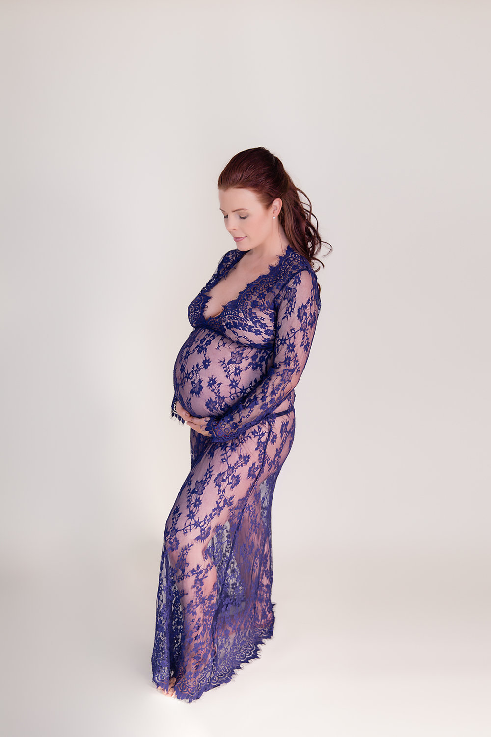 Mother to be in a blue lace gown. Maternity photoshoot in Calgary, Alberta