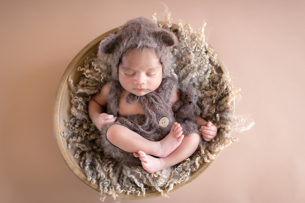Newborn baby boy dressed as a bear posed in a bowl. Newborn baby photoshoot ideas. Calgary Newborn Photographer - Milashka Photography