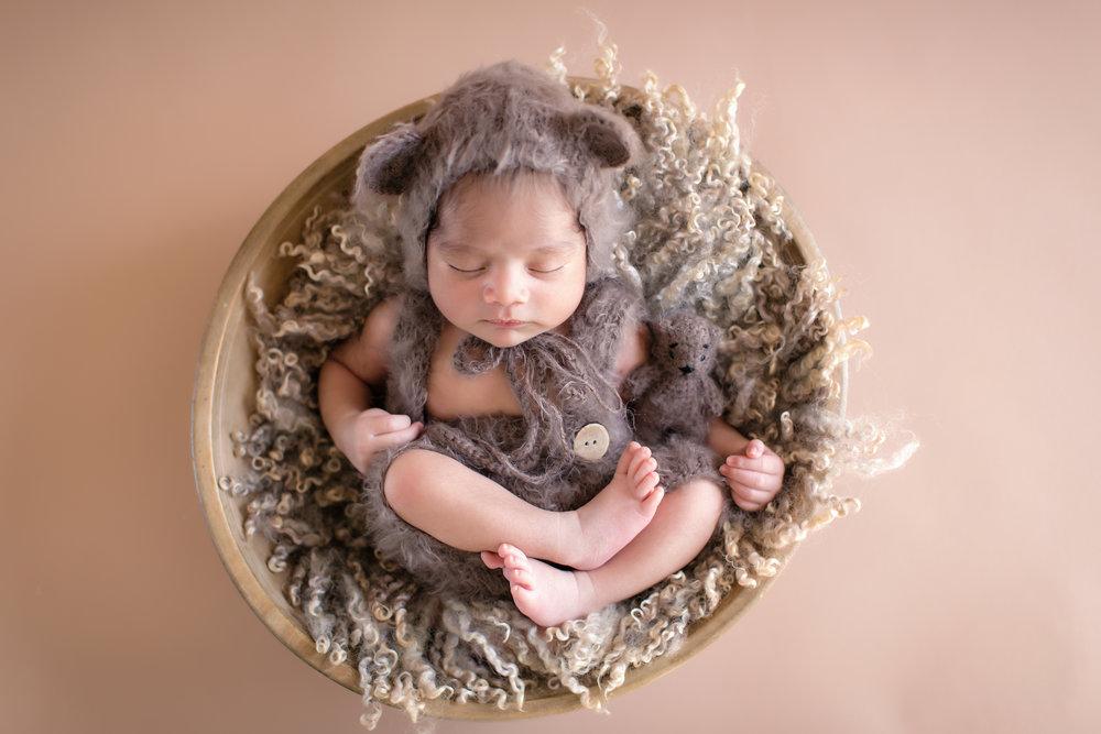 Newborn baby boy dressed as a bear posed in a bowl. Newborn baby photoshoot ideas. Calgary Newborn Photographer - Milashka Photography