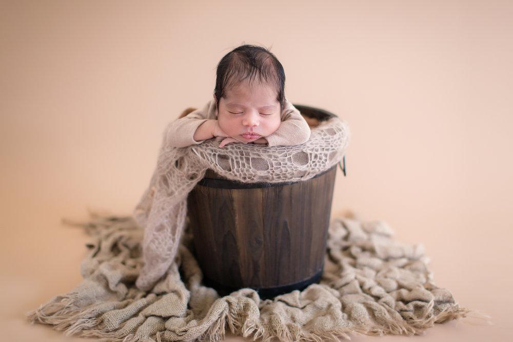 Newborn baby boy is posed in a bucket. Newborn baby photoshoot ideas - Calgary Photographer - Milashka Photography