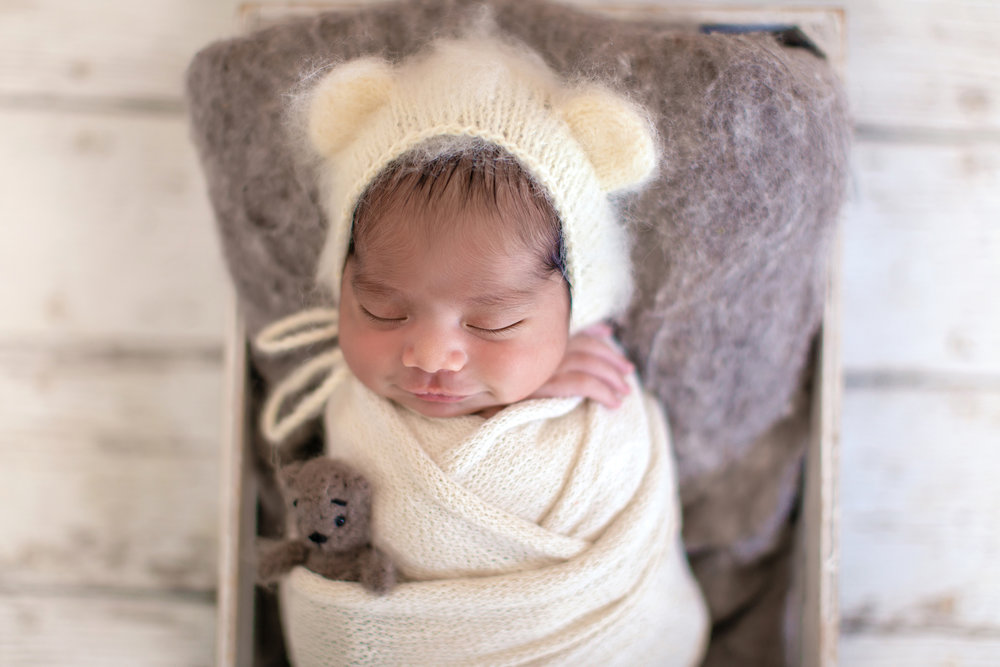 Newborn baby boy is sleeping soundly in a crate and smiling. He is wearing a bear hat and has a little bear toy with him. Newborn Photoshoot ideas - Calgary, YYC, Airdrie, Alberta baby and newborn photographer.