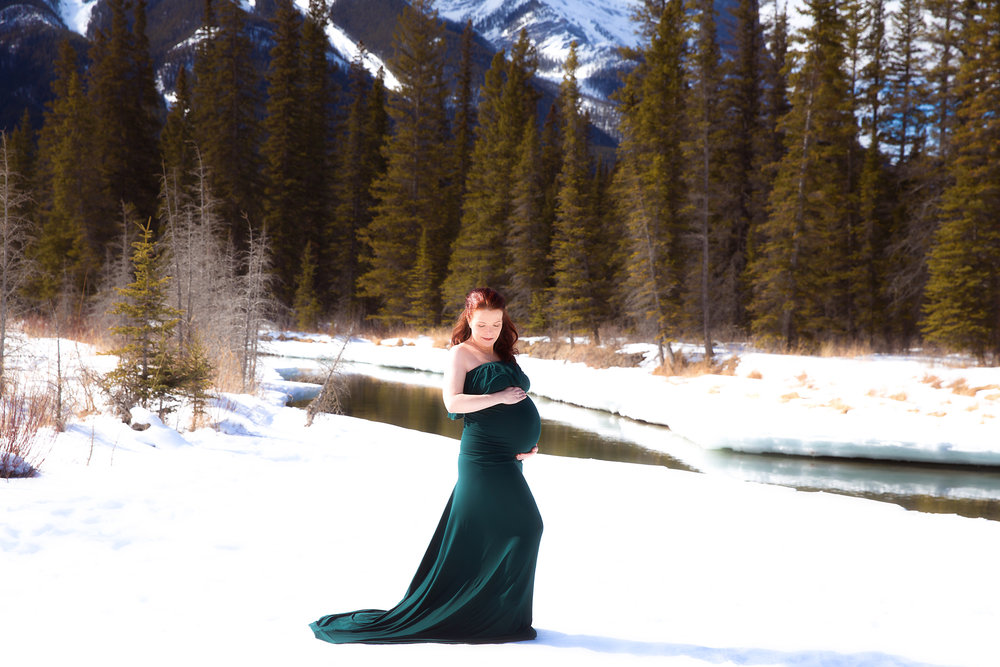 Mother-to-be is wearing a gorgeous green gown and is standing on a snow infront of a forest and river in Kananaskis Country. Calgary, Alberta maternity photographer - Milashka Photography