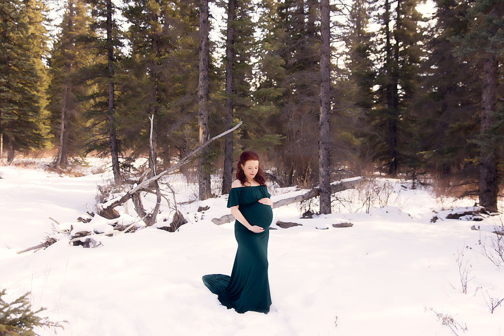 Expecting mother is wearing a green gown in the forest, standing on a snow. Maternity photoshoot ideas. Calgary Photographer - Milashka Photography