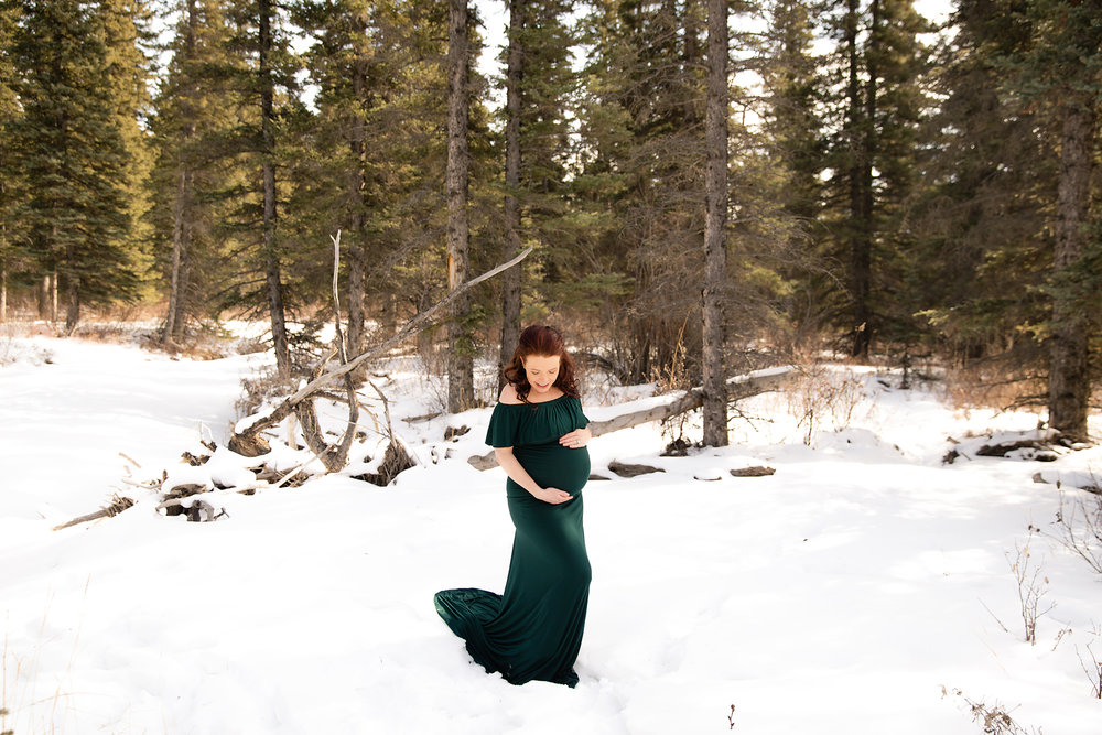 Mom-to-be is standing on a snow in a forest and wearing a green gown. Calgary and Airdrie maternity photographer - Milashka Photography