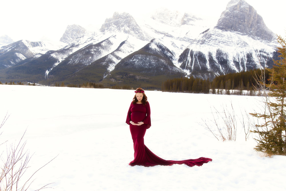 Mother-to-be is standing on a snow in front of Rocky Mountains and wearing a gorgeous red dress. Calgary Photographer specializing in Maternity portraiture - Milashka Photography