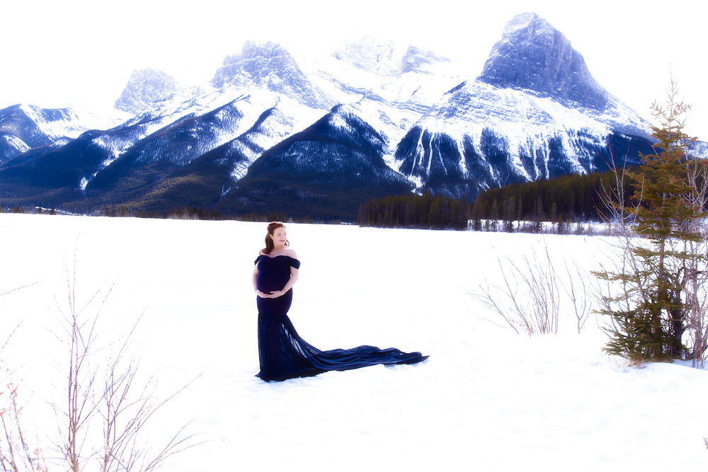 Mom-to-be in a blue gown standing on a snow with mountains in the background. Kananaskis maternity session. Calgary, Alberta maternity photoshoot