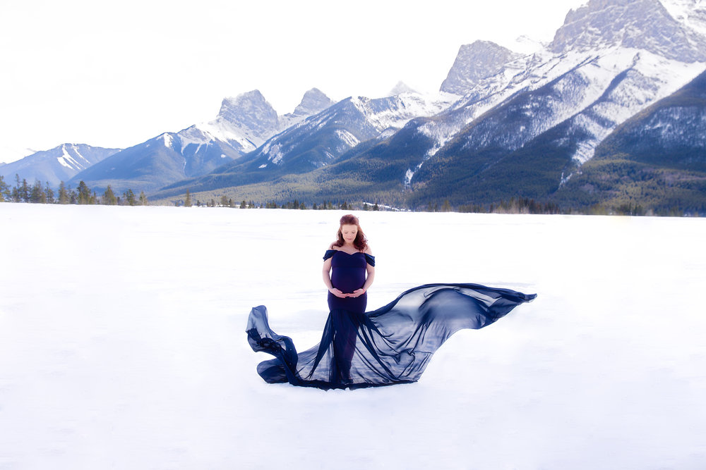 Mother-to-be is standing on a snow infront of Rocky Mountains wearing a blue dress. Calgary maternity photoshoot - Milashka Photography