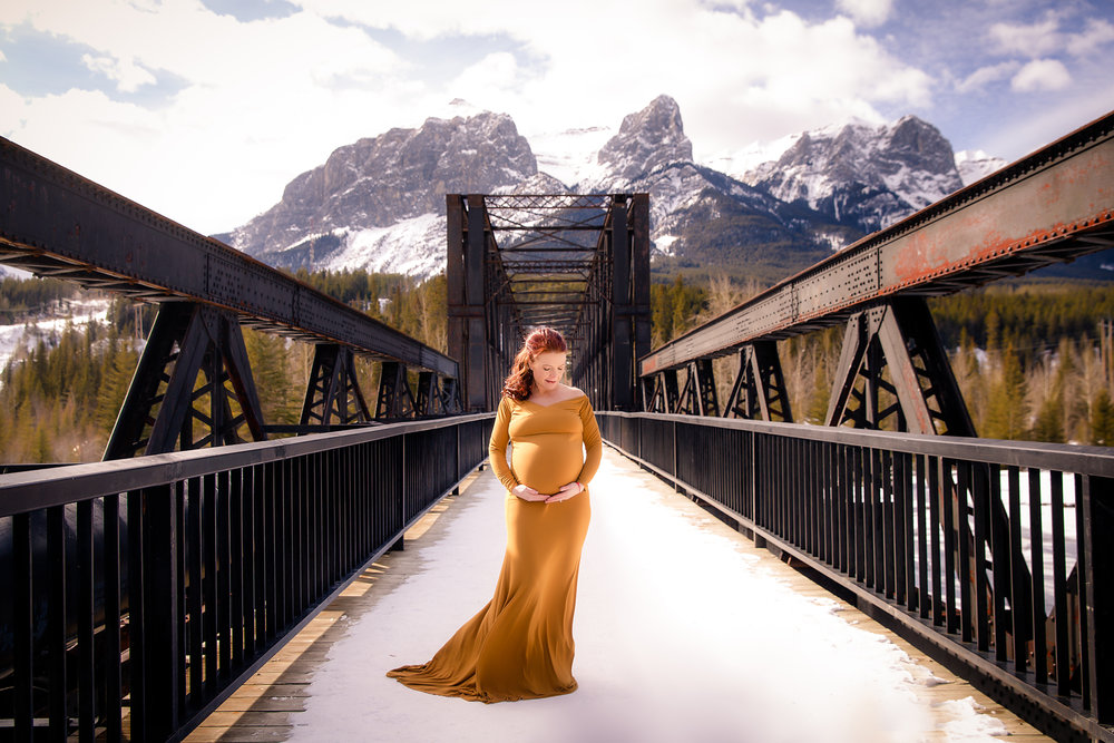 Mother to be is standing on a bridge wearing a mustard gown in Canmore, Alberta Canada.