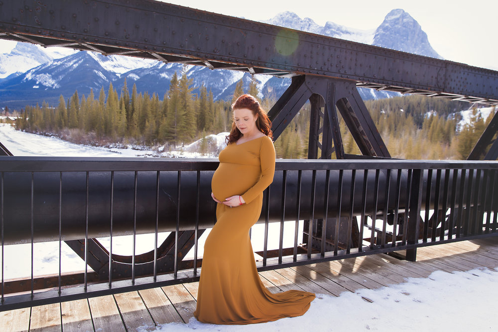 Mom-to-be in Canmore on a bridge wearing a mustard gown. Calgary photographer - Milashka Photography