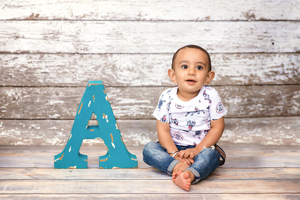 "Baby boy is sitting beside a giant letter ""A"" and smiling. Calgary baby photographer - Milashka Photography"