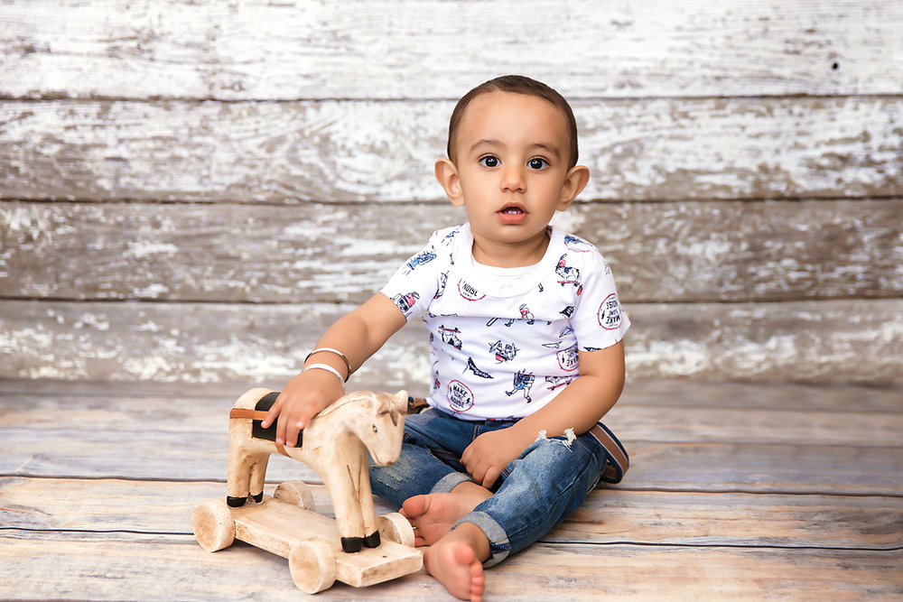Baby boy sitting on a floor with a wooden antique horse. Calgary and Airdrie baby photographer