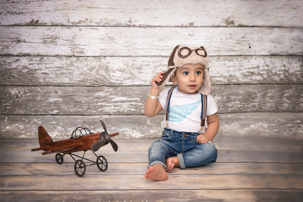 Baby boy is sitting on a floor and wearing an aviator hat with a little wooden plane beside him. Calgary baby photographer.