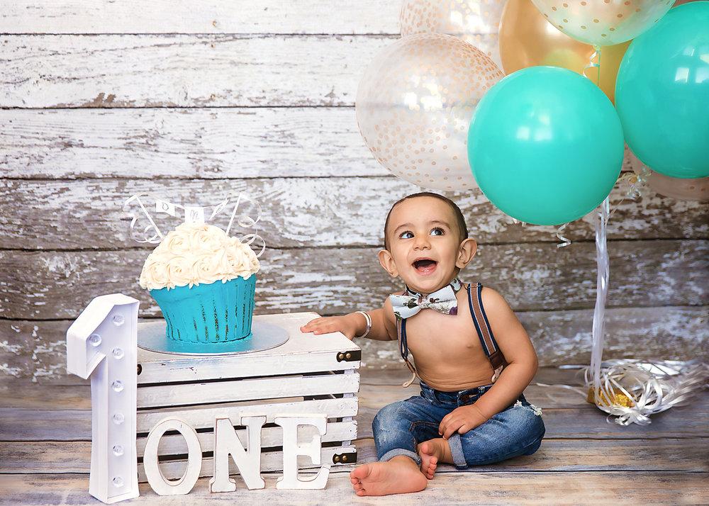 Cakesmash photoshoot idea. Little baby boy is sitting beside his cake and smiling. Calgary cakesmash photographer