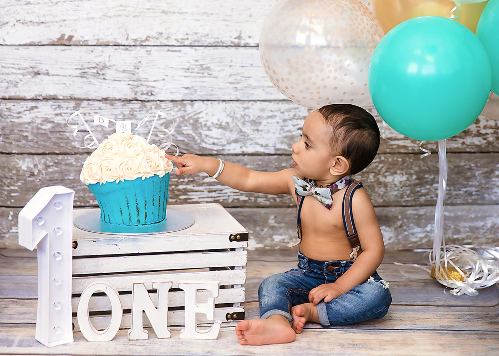 Little boy has his finger on his birthday cake - ready to taste the icing for the first time. Cakesmash photoshoot ideas. Calgary and Airdrie cakesmash and first birthday photographer.