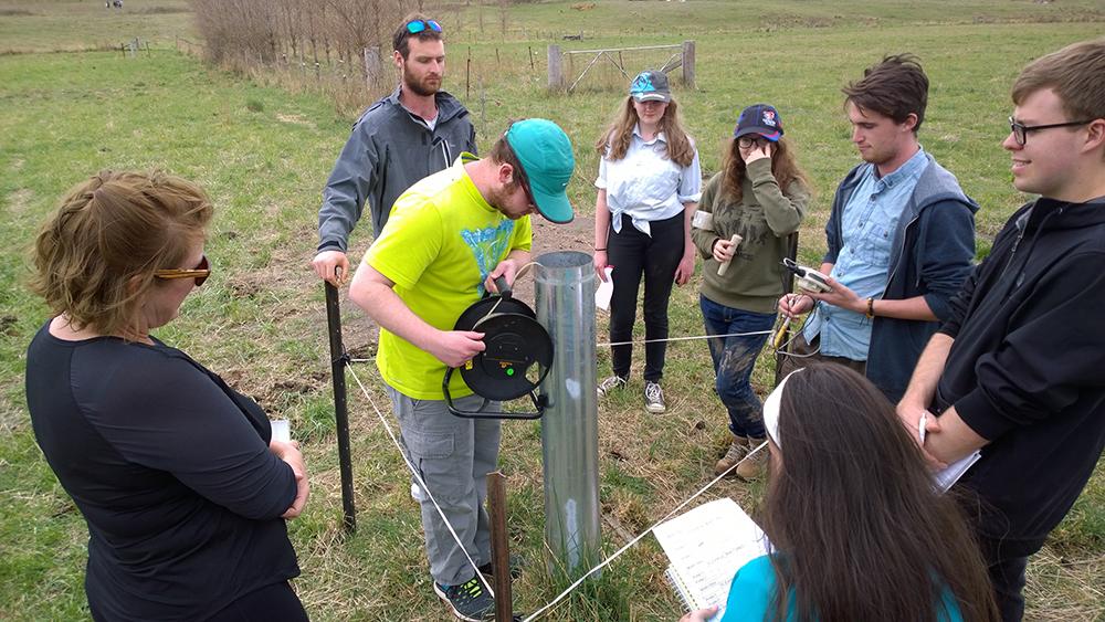 Measuring groundwater depth in piezometer using electronic measuring tape.