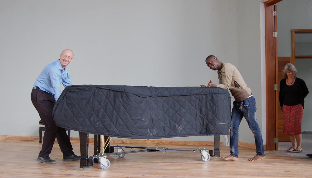 Randy Stubbs, CAC Programme Manager, and Abbas Haji, CAC Artist, move the piano onto the CAC performance stage for rehearsals in preparation of the chamber music concert.