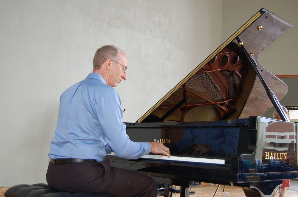 Randy Stubbs, CAC Programme Manager, plays the grand piano for the first time after it arrived from the United States of America. The piano is a gift from generous friends of the Music Department in America.
