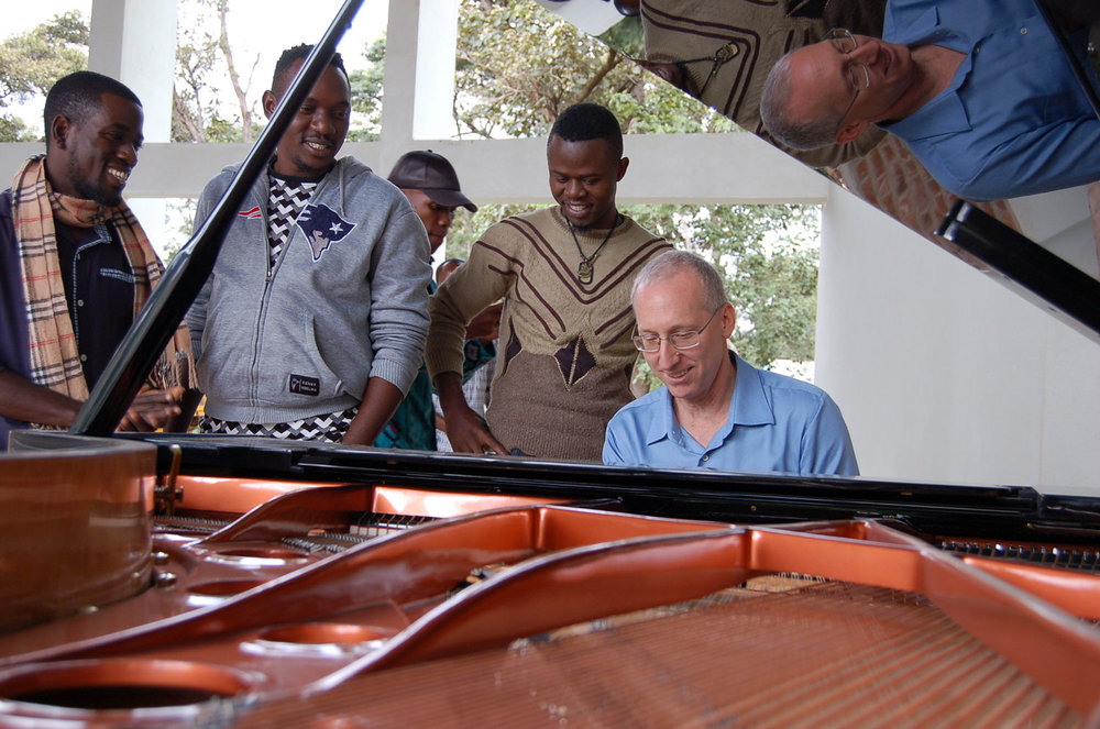 CAC artists admire the grand piano as Randy Stubbs, CAC Programme Manager, plays it.