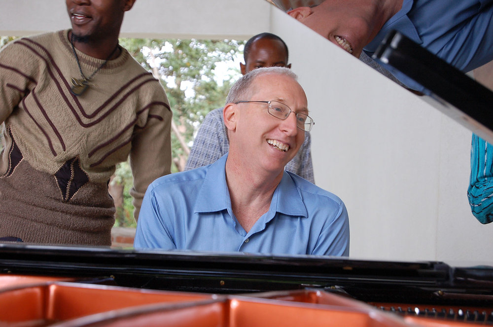 CAC Programme Manager smiles as he listens to the sounds of the grand piano that was donated to Tumaini University Makumira by generous friends in the United States of America.