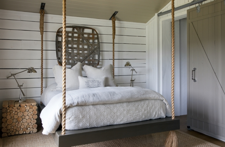 Rope swing bed in a farmhouse bedroom with shiplap wall, tobacco basket on wall, barn door, and cut log side table. Rachel Halvorson Inspired Decorating Tips. #farmhouse #bedroom #barndoor #ropebed #tobaccobasket #shiplap